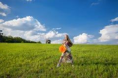 绿色领域的年轻美丽的女孩 免版税库存照片