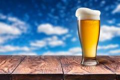 在玻璃的啤酒在反对蓝天的木桌上 免版税库存照片