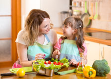 母亲和孩子烹调和获得乐趣在厨房里 免版税库存图片