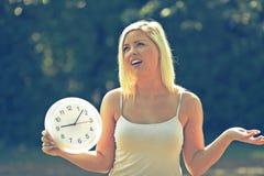拿着时钟和指向它的少妇由手指 免版税库存照片