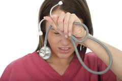 有听诊器的被注重的沮丧的翻倒年轻女性医生 库存照片