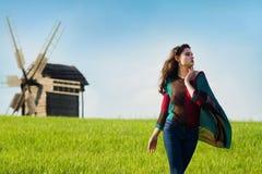有长的黑发的年轻美丽的女孩在绿色领域 免版税图库摄影