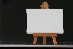 空白的帆布和木画架在便携式计算机上 库存照片