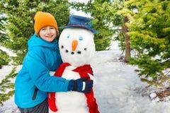 在冬日期间,男孩与红色围巾的修造雪人 免版税库存照片
