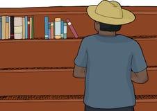 在帽子浏览书的男性 免版税库存照片