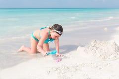 享受她的假期的儿童女孩通过使用在古巴美丽的海滩在海洋附近 库存图片