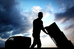 Составное изображение работника доставляющего покупки на дом нажимая вагонетку коробок Стоковая Фотография RF