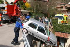 使用起重机的警察去除一辆被碰撞的汽车 免版税库存照片