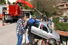 使用起重机的警察去除一辆被碰撞的汽车 免版税图库摄影