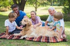 愉快的家庭在有他们的狗的公园 免版税库存图片