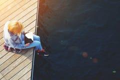 Γυναίκα τουριστών που ψάχνει τις πληροφορίες για την ταμπλέτα χαλαρώνοντας σε μια αποβάθρα Στοκ φωτογραφία με δικαίωμα ελεύθερης χρήσης