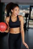 年轻愉快的女孩给逗人喜爱的微笑您,当解决在健身房时 免版税库存照片