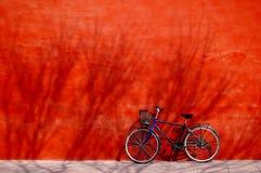 在墙壁之下的自行车红色 免版税图库摄影