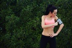 健康适合妇女在奔跑前调整她的在手机的个人教练员应用 免版税库存图片