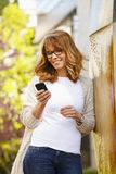 有巧妙的电话的可爱的妇女 免版税库存照片