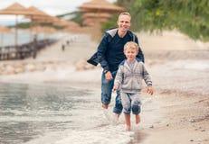 跑与他的父亲的小男孩在海浪线 免版税库存照片