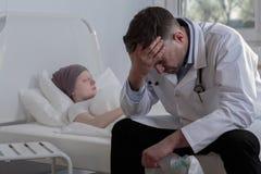 无能为力的医生和癌症孩子 免版税库存照片