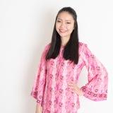 桃红色蜡染布礼服的亚裔女孩 库存照片