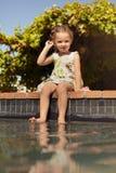 坐在游泳池边缘的逗人喜爱的小女孩 库存照片