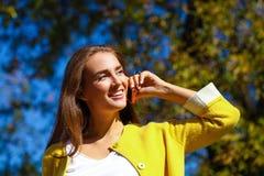 年轻美丽的愉快的妇女叫由电话在莫斯科 免版税库存图片
