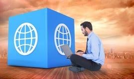 Составное изображение бизнесмена сидя на поле используя его компьтер-книжку Стоковое фото RF