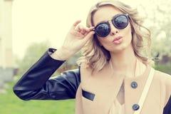 太阳镜的美丽的年轻性感的女孩走在城市街道上的一个明亮的晴朗的夏日的 库存照片