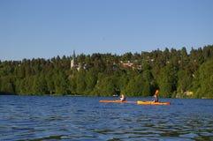 风景划独木舟的人的湖 免版税库存照片
