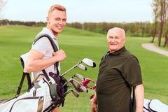 资深和年轻高尔夫球运动员用设备 免版税库存图片