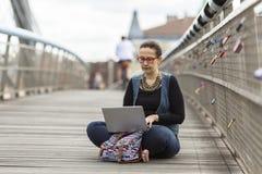 有膝上型计算机的妇女坐一座步行桥在一个老欧洲城市 免版税库存图片