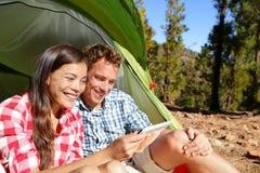 在帐篷的野营的夫妇使用智能手机 免版税库存图片