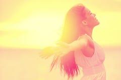 幸福-享受日落的自由的愉快的妇女 库存图片