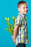 花男孩掩藏的花束在本身后的 免版税库存照片