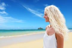 有长的卷曲金发的白肤金发的妇女在海滩 图库摄影