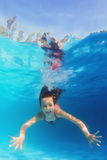 游泳在水面下在蓝色水池的年轻愉快的微笑的孩子 免版税库存图片