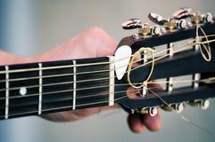 调整经典声学吉他的吉他弹奏者手 免版税库存照片