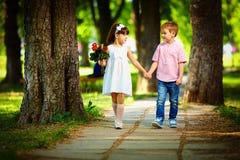 一起走在夏天公园的逗人喜爱的孩子 免版税图库摄影