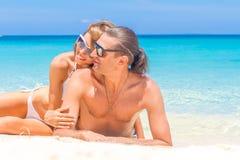 海滩夫妇查找 说谎在沙子的愉快的年轻夫妇在太阳下 库存照片