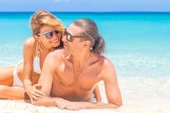 海滩夫妇查找 说谎在沙子的愉快的年轻夫妇在太阳下 免版税库存图片