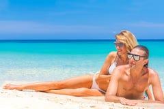 海滩夫妇查找 说谎在沙子的愉快的年轻夫妇在太阳下 库存图片
