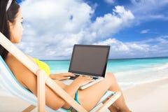 有膝上型计算机的愉快的妇女在海滩 免版税库存照片