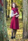摆在秋天森林里的女性时装模特儿画象室外 库存图片