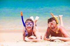 使有旅行的夫妇靠岸乐趣潜航,说谎在夏天海滩沙子用废气管设备 免版税库存照片