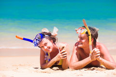 使有旅行的夫妇靠岸乐趣潜航,说谎在夏天海滩沙子用废气管设备 图库摄影