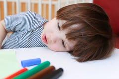 有毛毡的疲乏的小男孩写作休息他的在桌上的头 免版税图库摄影