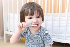逗人喜爱的小男孩在早晨清洗牙 免版税库存图片