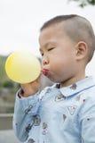 Воздушный шар мальчика дуя Стоковые Изображения