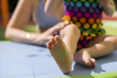 照顾握她穿在桌上的小的女儿脚五颜六色的泳装 免版税库存照片