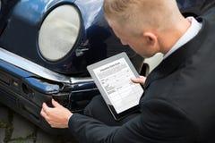 拿着数字式片剂的人审查损坏的汽车 免版税库存图片