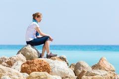 妇女坐与蓝色海天线的岩石 图库摄影
