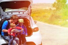 生与看地图的孩子,当旅行时 免版税库存图片